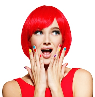밝은 빨간 머리카락과 여러 가지 빛깔의 손톱을 가진 젊은 예쁜 여자의 놀란 얼굴.