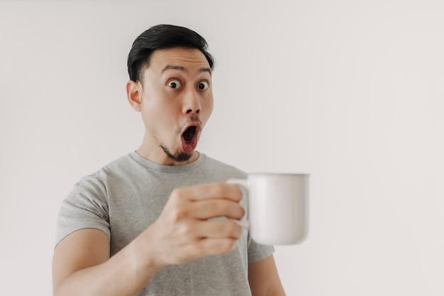 男の驚きの顔は白い背景で隔離のコーヒーを飲む