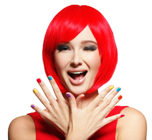 Surprised face of an young pretty woman  with bright red hairs and multicolor nails.