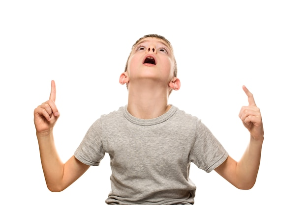 Surprised fair-haired boy in a gray t-shirt stands and points with the index fingers up.