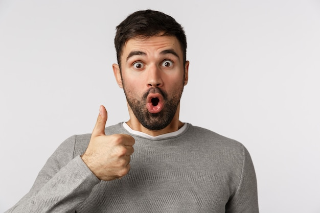 Surprised and fascinated, amazed speechless bearded guy in grey sweater react to wonderful amusing event, show thumb-up in like, approval or accepting gesture, gasping say wow