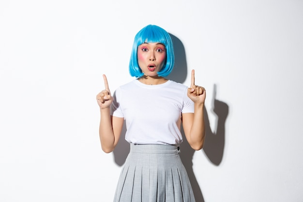 Surprised and fascinated asian girl in blue short wig, kawaii makeup, looking impressed and pointing fingers up, showing logo or promo banner, standing.