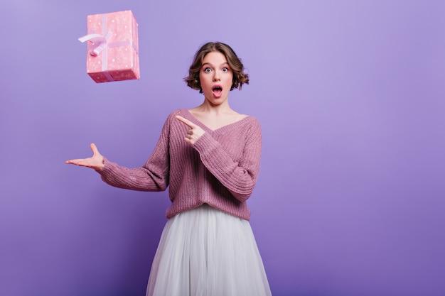 Удивленная очаровательная дама позирует с фиолетовым интерьером с новогодним подарком. крытый портрет красивой девушки с короткой стрижкой, выражающей изумление во время фотосессии с подарком.
