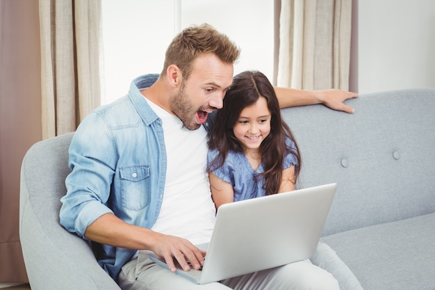 Surprised father and daughter using a laptop