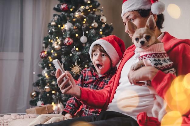 Удивленный отец с ребенком и щенком в шляпах санты, держащий сотовый телефон