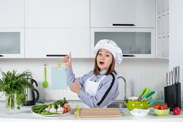 びっくりした女性シェフと新鮮な野菜を調理器具で、白いキッチンの右側で大丈夫なジェスチャーをする