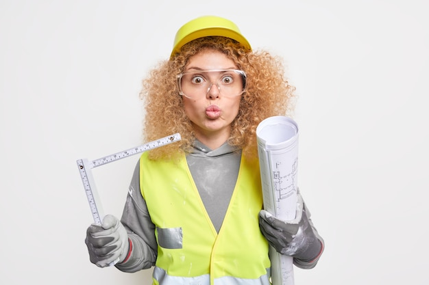 Surprised female engineer with curly hair keeps lips folded works on construction of new building holds rolled blueprint under arm and tape measure wears safety clothes poses indoor. engineering