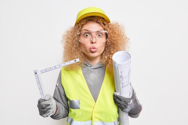 巻き毛の驚いた女性エンジニアは、唇を折りたたんで新しい建物の建設に取り組んでおり、腕の下に巻尺を保持し、巻尺は屋内で安全服のポーズをとっています。エンジニアリング