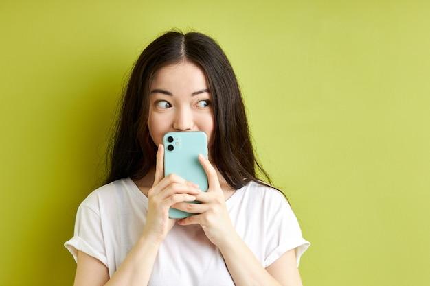 녹색 파스텔 배경에 고립 된 sms 메시지를 읽고 놀란 여성 숨기기, 뭔가를 읽은 후 충격에 서서, 캐주얼 흰색 티셔츠를 입고, 측면을보고 서