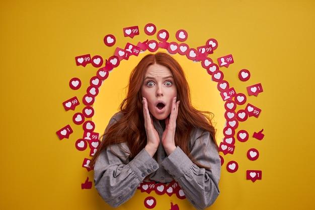 Удивленная женщина в шоке от комментария в блоге или посте дает эмоциональную реакцию. портрет желтой стены студии