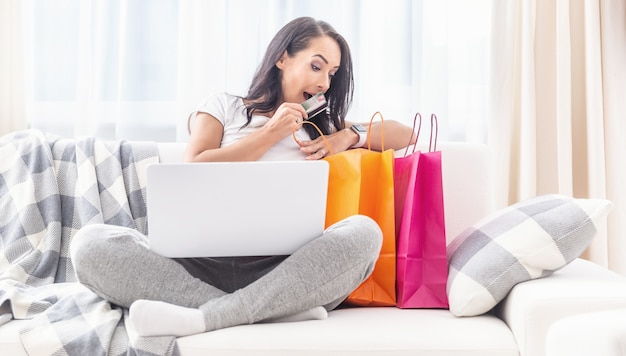 Surprised female looking into orange and pink paper bags next to her on a white sofa, with credit card in her hand and a computer in her lap.
