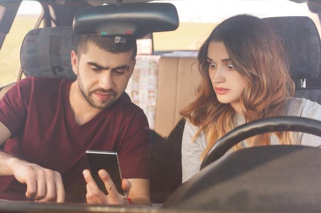 Удивленная женщина смотрит на смартфон