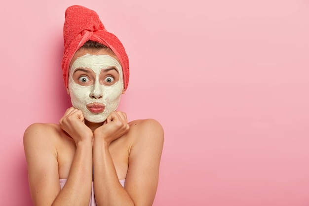 Surprised female model wears white clay mask, keeps hands under chin, shows bare shoulders and healthy skin, looks at herself in mirror, poses at bathroom against pink wall