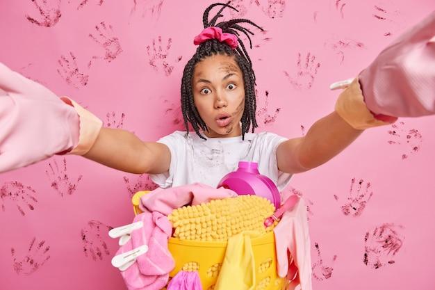 머리 띠가있는 놀란 여성 모델은 분홍색 벽에 집안일로 바쁜 집안일을하는 동안 카메라에 더러운 얼굴과 옷이있는 셀카를 쳐다보고 팔을 뻗습니다.