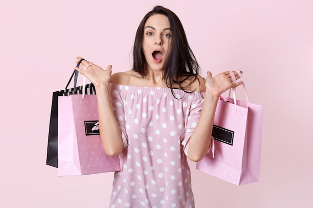 Surprised female shopaholic dressed in stylish dress, holds bags in two hands, forgets buying something, feels shocked to see big discounts at shop, isolated on pink wall