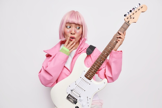Surprised female soloist looks stunned at electric acoustic guitar plays music being famous rock star going to record musical performance wears pink jacket gloves