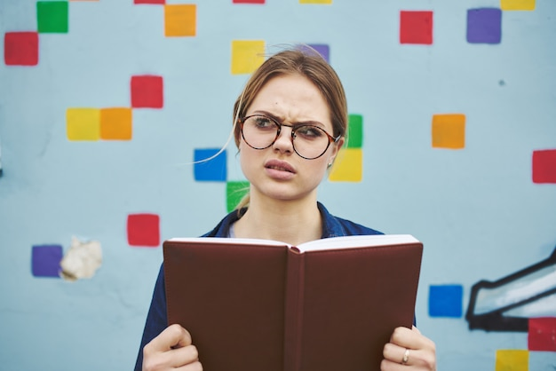 本を持って路上で眼鏡をかけて驚いた女子学生