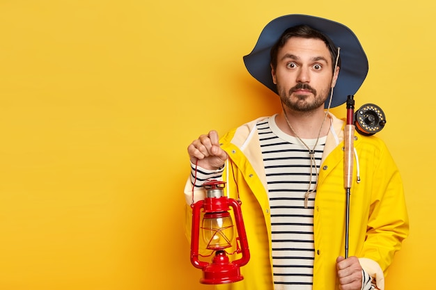 Surprised fisherman holds fishing rod and kerosene lamp, has overnight fishing trip, wears hat and raincoat, poses over yellow wall