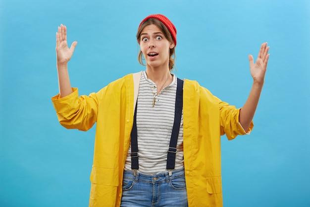 그녀가 각도 물고기의 손 길이를 보여주는 캐주얼 옷에 놀란 된 어부. 큰 무언가의 크기를 보여주는 노란색 아노락과 진 바지를 입고 놀란 아름다운 여성.