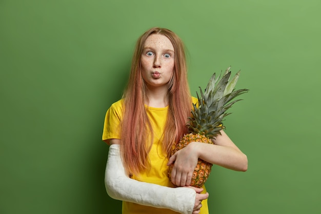 Ragazza lentigginosa sorpresa con labbra arrotondate, detiene un delizioso ananas succoso, indossa un gesso sul braccio rotto, vestito con una maglietta gialla, posa contro il muro verde, ha bisogno di cure mediche, ha la mano nella benda