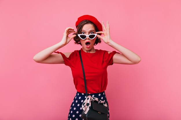スタイリッシュなサングラスのポーズで驚いたフランスの女の子。赤い服を着たエレガントな白人女性の屋内写真。