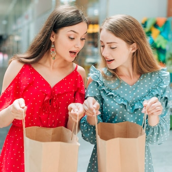 Surprised friends looking at shopping bags