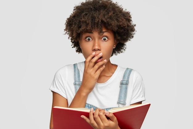 La ragazza nera spaventata sorpresa copre la bocca dallo stupore