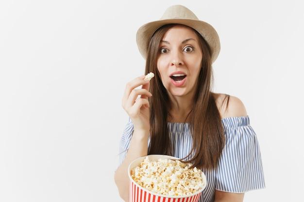파란 드레스를 입은 재미있는 여자, 흰색 배경에 격리된 양동이에서 팝콘을 먹는 영화 영화를 보고 있는 모자. 사람들, 영화의 진지한 감정, 라이프 스타일 개념. 광고 영역입니다. 공간을 복사합니다.