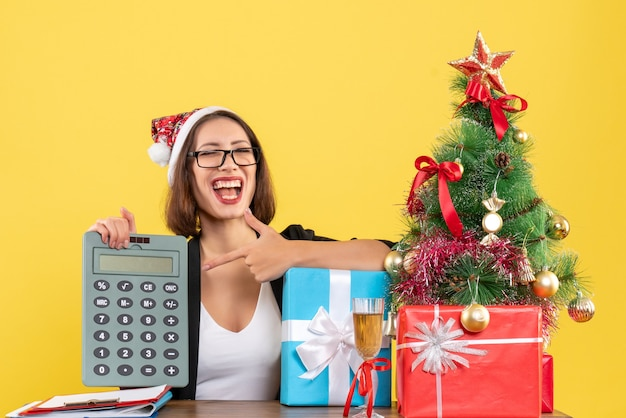 Signora affascinante divertente sorpresa in vestito con il cappello di babbo natale che mostra calcolatrice nell'ufficio su colore giallo isolato