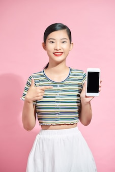 Surprised funny lady telephone hand indicate finger screen advertising new gadget model isolated pink