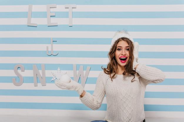「雪を降らせて」というレタリングでポーズをとる変な顔の驚いた、面白いモデル