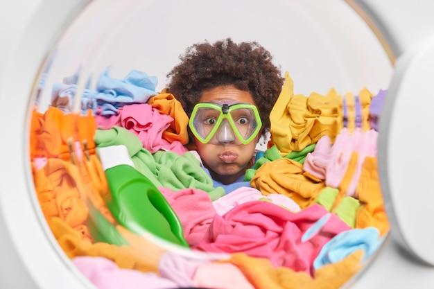 곱슬머리를 하고 뺨을 불고 있는 놀란 재미있는 여성은 입술을 둥글게 유지하고 세탁기 내부에서 다이빙하는 척 세탁 포즈에 묻힌 스노클링 마스크를 착용합니다