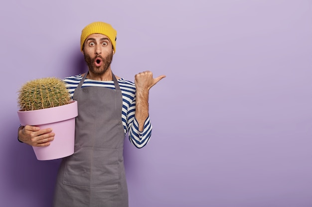 Удивленный садовник позирует с большим кактусом в горшке
