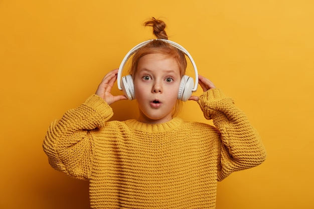 Surprised ginger kid listens audio track in headphones, impressed by loud sound, opens mouth with wonder, wears oversized knitted sweater, isolated on yellow wall. children and hobby concept