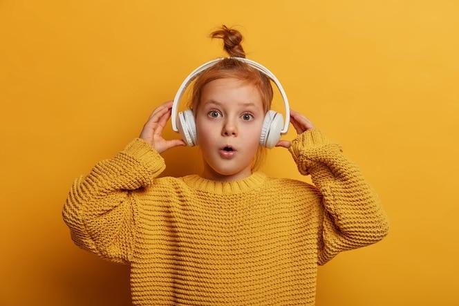 惊讶的姜孩子戴着耳机听音轨,被响亮的声音所震撼,惊奇地张开嘴,穿着超大号的针织毛衣,孤立在黄色的墙上。儿童与爱好概念