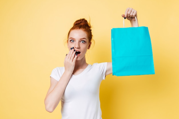 Surprised ginger woman holding packet in hand and covering mouth
