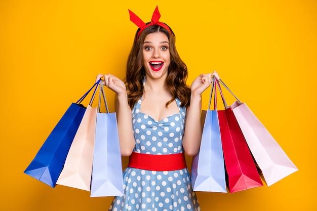 Удивленная девушка, увлеченная покупателем, кричит, показывает сумки для покупок на желтом фоне