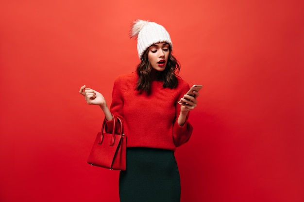 Surprised girl in bright sweater and white cap holding smartphone on isolated wall