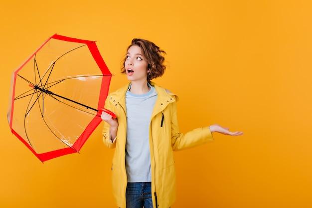 Ragazza sorpresa in cappotto che osserva in su e che tiene l'ombrello. giovane donna scioccata con ombrellone isolato sul muro arancione brillante.