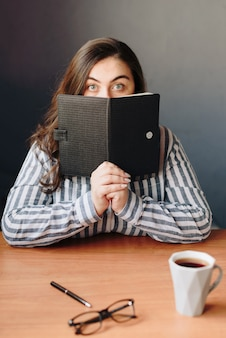 The surprised girl covers part of her face with a black notebook