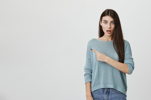 Surprised girl drop jaw and pointing left astonished