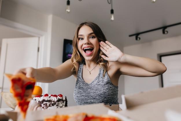 Удивленная девушка ест пиццу с помидорами. внутреннее фото довольно белой женщины, наслаждающейся фаст-фудом утром в выходные.