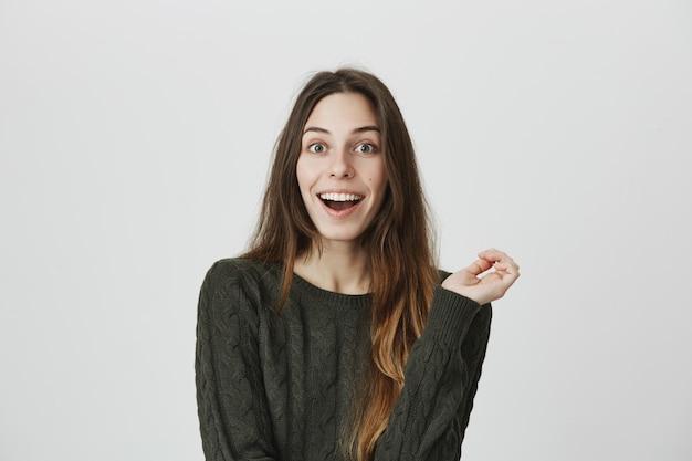 Удивленная девушка слышит интересные новости, открытый рот взволнован и улыбается