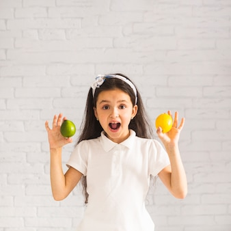 Surprised girl holding lime and lemon in her two hands