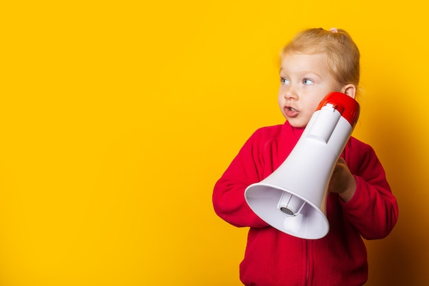 Surprised girl holding a megaphone on a bright yellow background.