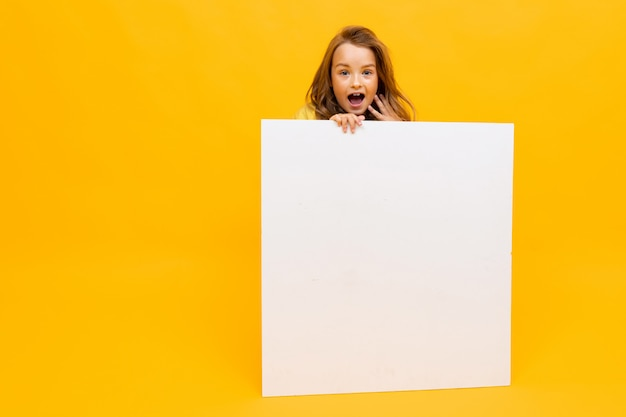 Surprised girl holds an advertising poster with a mockup on a yellow background
