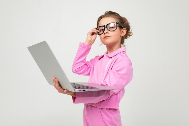 ピンクのスーツを着た驚いた少女は白いスタジオの壁にラップトップでニュースを読む