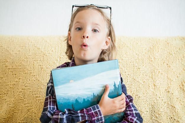 격자 무늬 셔츠와 안경을 쓴 놀란 소녀는 온라인 학습을 통해 손에 책을 들고 있다