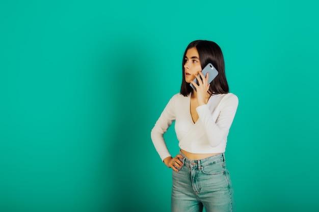 青い表面に隔離された携帯電話で話しているカジュアルな服を着て驚いた女の子。