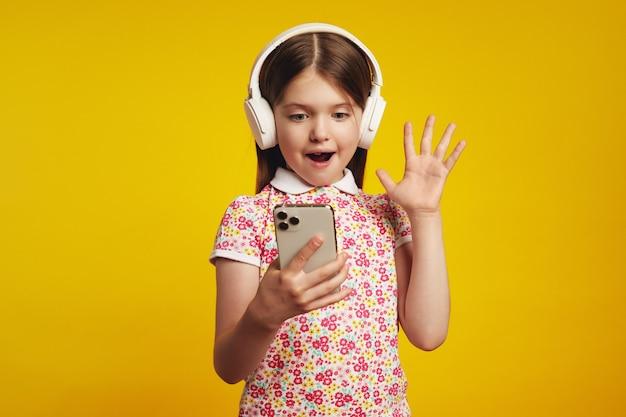 Удивленная девушка в наушниках держит телефон, рада получить уведомление